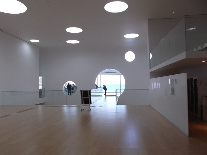 白を基調としていて、すっきりとした館内。吹き抜けの天井から差し込む陽の光がやさしく照らしています。窓の向こうに見える海の色も白い壁に映えてとてもキレイです。  アートに詳しくない方も、おしゃれな空間を楽しむ感じで訪れてみてはいかがでしょうか?