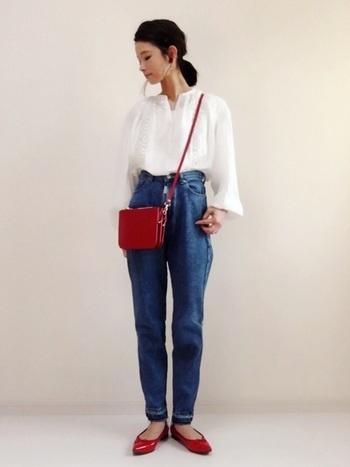 赤いバッグと赤いフラットシューズがキュートなコーデ。シンプルな白シャツ×ハイウエストデニムのシンプルなコーデがぐっと可愛らしい印象になる赤の使い方ですね。