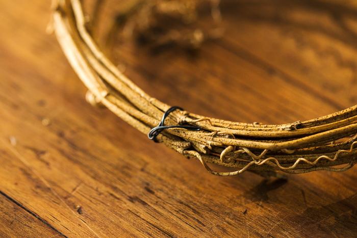③ねじって固定したワイヤーの先端は尖っているため、傷つかないように蔓の束の中へ差し込みます。