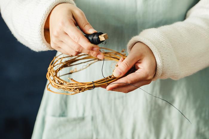 ④新たにワイヤーを約10cmほど伸ばし、蔓に巻きつけます。ここからグリーンの巻きつけを開始。伸ばしておいたワイヤー部分はフックなどに掛けるための輪になります。