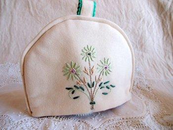 ウール生地に花の刺繍が入った手作りの「ポットカバー」。中綿が詰められているので保温性もあります。細やかな刺繍と、ちょこんと付いた持ち手部分が愛らしいですね。