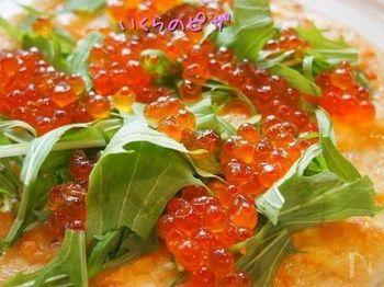 ピザはトッピングしてから焼く方法がよく見られますが、チーズだけのせて焼いてから仕上げにトッピングする方法もありますよ。こちらはイクラと水菜をのせた新鮮レシピです。イクラとチーズの意外な相性をお試しあれ♪