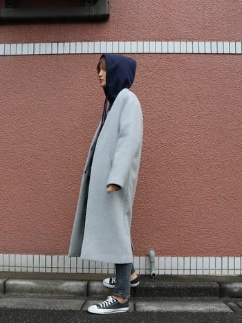 シンプルなノーカラーコートにパーカーを合わせたメンズライクなワンマイルコーデ。大きめのフードをかぶってこなれ感のある雰囲気です。