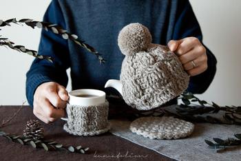 ティーコージーはティーポットにかぶせて保温する為の道具です。別名「ティーコゼー」とも呼ばれます。こちらはハンドメイドならではの温かみのある編み目と、大きなボンボンが可愛らしいですね。ポットがすっぽり帽子をかぶっているシルエットに冬らしさを感じます。
