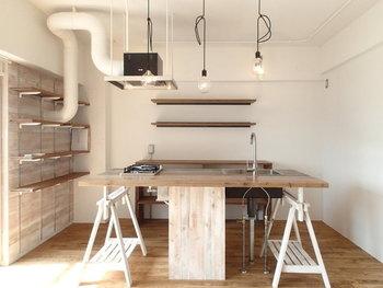 対面式のキッチンは、ナチュラルな質感の木を贅沢に使用した作り。天板の両側には、棚も兼ねた真っ白な支えが付いています。ダクト管までホワイトで仕上げられているところに、リノベーションの醍醐味を感じます。