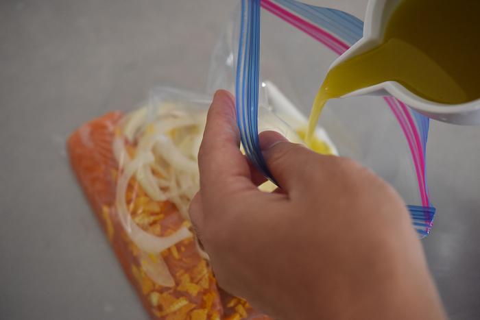 漬け込みには市販の保存袋が便利。サーモンと一緒に刻んだゆずの皮と玉ねぎを入れ、マリネ液を注ぎます。空気を抜くように封をして冷蔵庫へ。最低1時間は寝かせて味を馴染ませましょう。