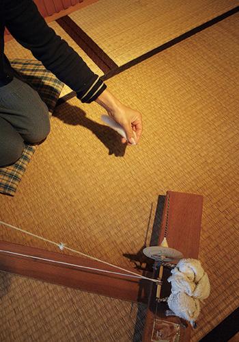 摘み取った綿は紡ぐことで糸になります。繊維をほぐした綿を軽くもち、引き出していくと繊維が繊維を呼び糸状に続いていきます。これにヨリをかけ巻き取ることで糸として使えるようになります。綿の繊維に綺麗にヨリをかけ、均一な糸にする作業は技術がいる職人技。写真は手回し糸車で糸を紡いています。