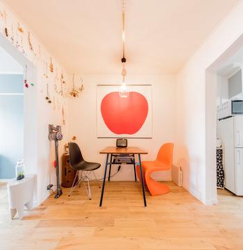 きれいな色のデザインポスターを、壁の一面に飾るのも素敵。オレンジのチェアもポップで可愛いです。