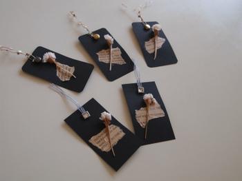 黒の画用紙に、ドライフラワーや洋書をちぎったものを貼りつけて、シックなデザインのタグに。