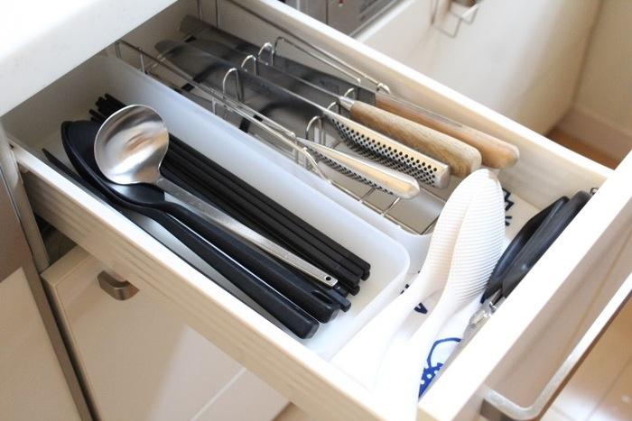 キッチンのコンロのすぐ横の引き出し。使う頻度の高いキッチンツールをまとめて収納しているそうです。包丁は、横置きできる貝印の包丁たてに収納。包丁どうしが重なりあったりぶつかったりしないので、刃が痛みにくく取り出しやすいメリットがあります。