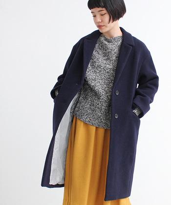 メンズライクなネイビーのチェスターコートと、イエローのスカートを組み合わせたコーディネート。前のボタンを閉めたときにもちらっと見えるキレイなイエローとネイビーの配色がバランス良いですね。女性らしいきれいな印象に仕上がっています。