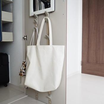 扉の裏側も収納スペースに大変身!こちらはバッグを提げておくアイディア♪フックの種類によっていろいろな物をしまえるようになりますね。