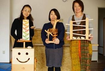 左から、児童養護施設での木育キャラバンで使う木のおもちゃを手にした『love lotus』代表の蒲田ちかさん。右に、チョコレート作りに協力した「こまつ町家文庫(古本とカフェ)」代表の金田奈津代さん、「NPO法人Lotusの」理事長の山口巴さん。