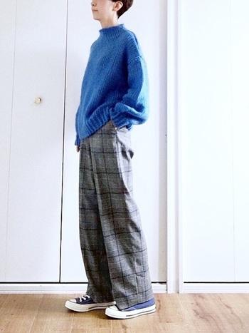 グレーベースのチェックパンツは、ブルーのニットを合わせて爽快なスタイルに。スニーカーもブルーにして、全体に統一感を持たせます。