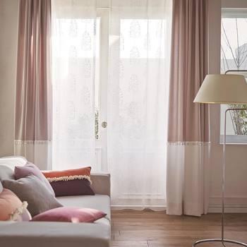 淡いピンクが優し気なツートンカラーのカーテンと美しい詩集集が施されたレースのカーテンを組み合わせたリビング。淡い光に包まれながら、ゆったりとした時間が過ごせそう…。