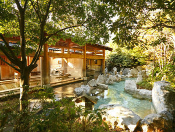 """広い敷地の中央には、立派な大湯殿!大浴場は8種用意されており、二本の自家源泉から注がれるかけ流しの湯を楽しめます。高アルカリ性泉質のため、""""美肌の湯""""として人気。貸切露天風呂もありますよ。"""