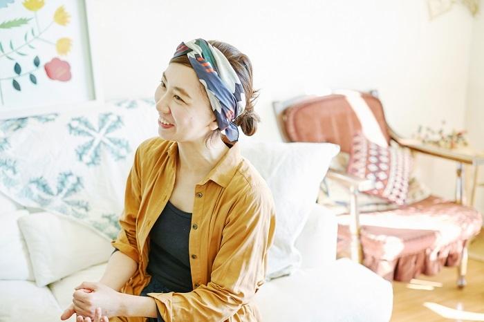 頭に巻いているのは、安原さんの絵が印刷されたスカーフ。太陽のようなやさしい笑顔がいっそう華やぎます