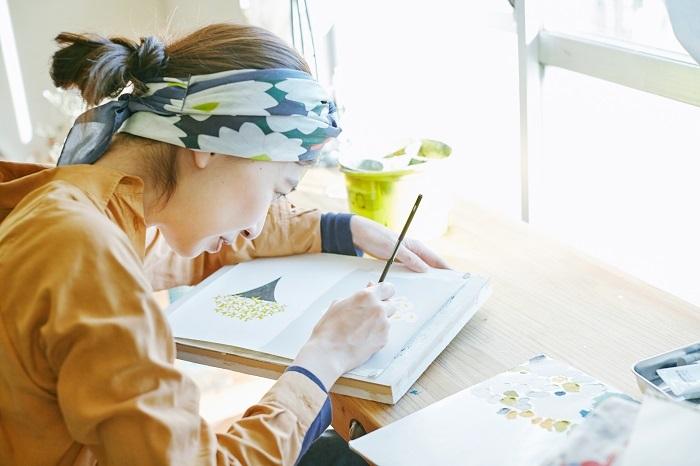 ぎゅっと身体を縮めて目を凝らすように細かい箇所に筆を重ねていきます