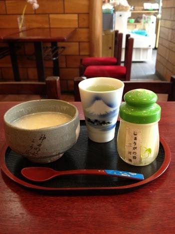 """三河屋綾部商店の「延寿甘酒」。器に""""神田明神""""と書かれているのが粋ですね。米、糀、水だけで作る甘酒は、酒粕で作るものよりも飲みやすく、甘酒初心者の方にもおすすめです。生姜パウダーを振りかければ、また違った味わいも楽しめます。器にたっぷり入っていて飲みごたえがあるのもうれしいですね。"""