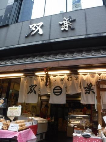 """「豆腐の双葉」は、人形町駅をおりてすぐにある""""甘酒横丁で食べ歩きをするならここ!""""と言われるほど有名なお店。明治40年に東京・深川で創業後、昭和23年にここ人形町に移転しました。店頭には、お豆腐やがんもなどの商品がたくさん並んでいます。"""