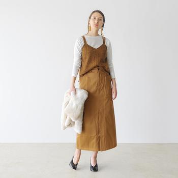 タイトなロングスカートに、白のぴったりトップスとキャミソールを合わせたスタイルです。キャミソールとスカートの色を合わせてセットアップ風にすることで、縦長のラインをより強調することができます。