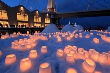 続いては、青森市の「あおもり雪灯りまつり」です。会場は青森駅すぐ近くにある、ねぶたの家ワ・ラッセ西の広場。雪燈籠が幻想的に並んでいますね。このお祭りの特徴は、市民参加型だということ。この雪燈籠も市民が作ったもので、ほかにもキャンドルホルダーに願い事を書いて飾るなどといった体験もできます。