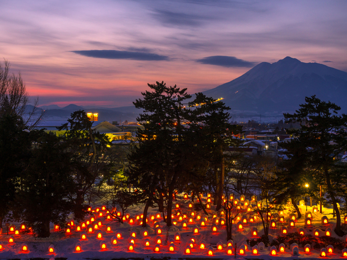 弘前城本丸から岩木山に向かう蓮池周辺には、ご覧のようにローソクを灯したかまくら灯篭がずらり。岩木山をバックにした荘厳で、あたたかみのある美しさに、寒さを忘れてしまいそうですね。