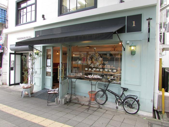 フランスの街角にあるようなかわいらしい店構えの「プラス ドゥ パスト」。神戸駅から徒歩5分ほどの、楠木正成公を祀る湊川神社のそばにあり、水色のうつくしい外観が目を惹きます。南仏の空と海をイメージしているそうで、南仏で修行されていたオーナーさんのこだわりが感じられますね。パンが並ぶ店内も外観と同じカラーで統一されています。
