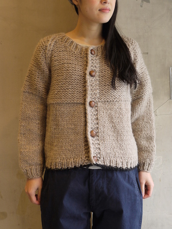 ざっくりとした質感と、ボタンのデザインがナチュラルな印象のカーディガンです。編み模様の切り替えがアクセントになっています。