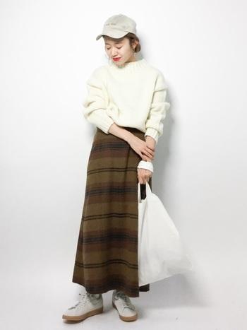 シンプルな白ニットに、チェックのロングスカートを合わせたコーディネートです。スカートを主役に、他をホワイトでそろえることで、軽やかな印象になっています。