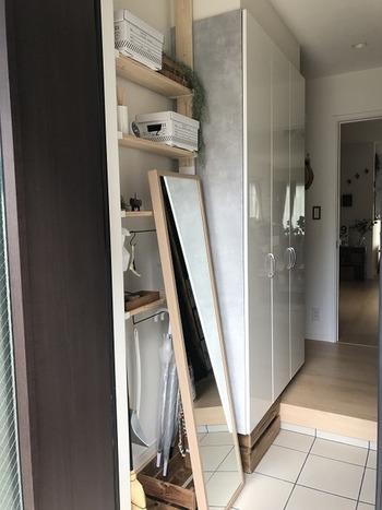 小さな玄関で収納が足りないなら作ってしまいましょう!姿見を立てかけた棚の下部分に傘や掃除道具などを収納すれば、オシャレに目隠しできちゃいます。