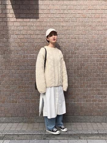 白のシャツワンピースに白のアラン模様のセーターを重ねて。キャップは被ると顔に影を落としてしまうけれど、ベージュ系や白系を選ぶことで、明るく清潔感ある表情になります。