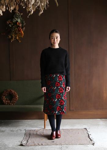 黒のニットに、レトロな花柄のタイトスカートを合わせた着こなしです。赤の花が目を惹きますが、ベースの色は黒系でまとめられているので、縦長のIラインをしっかりアピールできるスタイリングになっています。