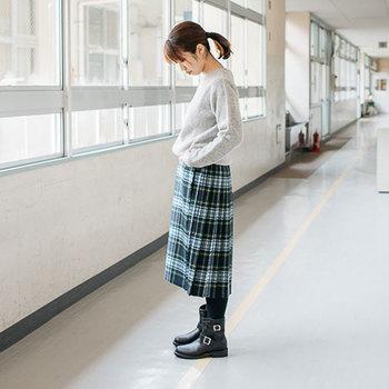 セーターとタータンチェックの巻きスカートというオーソドックスなスタイルに、エンジニアブーツを合わせて。足元にボリュームを出すことで、全身のバランスがよく、きれいにまとまっています。