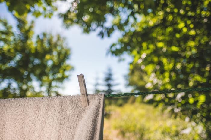 バスタオルなど大きくて吊るし干しがむずかしい場合の干し方です。縫い代はとくに厚みがあり乾きにくい部分ですので、重ならないように干すのがポイントに。 半分を目安に掛けたら片側の片方の角が下にくるよう大きく斜めにずらします。片側もつられて自然にこのような形になるので、下側がWの形に見えると思います。こうすると下りてくる湿気が角だけに集中するので、乾きが早くなるのだそう。毛布やラグにも使える干し方ですよ。