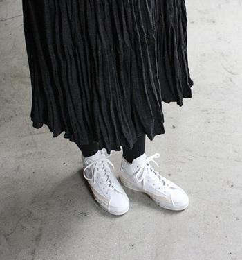 ハイカット×レザーの大人顔スニーカーはプリーツスカートを主役にした上品コーデにも良く似合います。真っ白のスニーカーを引き立たせるために、スカートもタイツも黒でまとめるとシックで素敵。