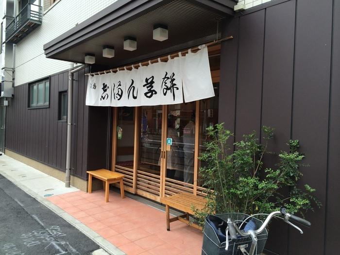 """スカイツリーから隅田川沿いをしばらく歩くと見えてくる「志""""満ん草餅」は、墨田区・向島で知らない人はいないほど有名なお店。大通り沿いの大きなのれんが目印です。"""
