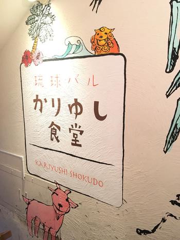 """JR恵比寿駅から徒歩1分ほどのところにある「琉球バル かりゆし食堂」は、ほっこり和む手描きのイラストが可愛い外観のお店。店名の「かりゆし」は、沖縄の方言で""""おめでたい""""という意味。ここでごはんを食べたら、なんだか楽しい気分になれそう。"""