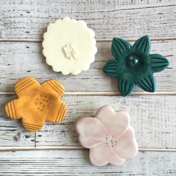 アンティークボタンのような雰囲気のブローチ。やまぶきの花をモチーフに、上品で清楚な印象に仕上げています。とても軽いので、薄手のカーディガンやニット帽にも。