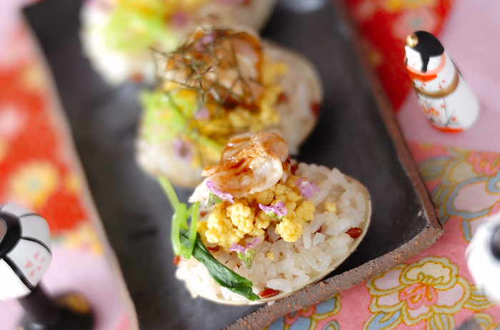 ひな祭りといえば、はまぐり。そこで、大はまぐりを殻ごと使ってしまう素敵なアイデア♪貝殻に寿司飯と卵、結んだ三つ葉をのせ、タレを塗ったはまぐりを。黒い和皿に盛り付けると、引き締まって格調が感じられますね。