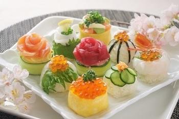 サーモン、ひらめ、まぐろ、いか、海老、いくら…豪華な魚介で華やかな手鞠寿司にするのも、ひな祭りらしくていいですね。お刺身を薔薇づくりにしてのせるのも素敵。手鞠型にした寿司飯に、薄焼き卵やきゅうりを巻き付けていますね。