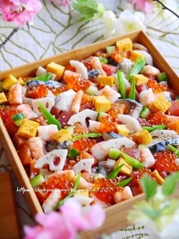まず、寿司飯に海苔とごまをたっぷりと。次に野菜と卵焼きをのせますが、仕上げの彩り用に少し残しておきます。そこに、刺身や海老などをバランスよく置き、仕上げ用の彩り野菜と卵をトッピング。最後にいくらをところどころに配置し、白ごまと絹さやを飾ります。