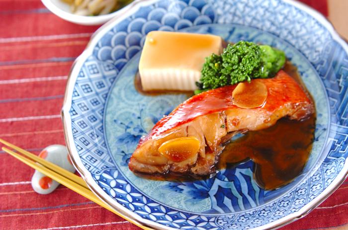 家庭でもできるなら、食べてみたい金目鯛。箸でふわりとほぐれる身の柔らかさを楽しむには火力の調節がカギです。  ここで添えてあるのは、菜の花と豆腐。金目を煮た後の煮汁でさっとお豆腐を煮て、菜の花は煮汁を絡めて。旨味が美味しい一皿です。