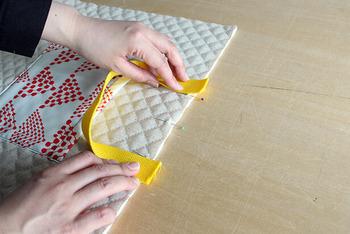 さらに、持ち手もキルティング側に付けます。写真のようにひもを1㎝ほどはみださせて縫い付けることで、重いものを入れてもはずれにくくなります。