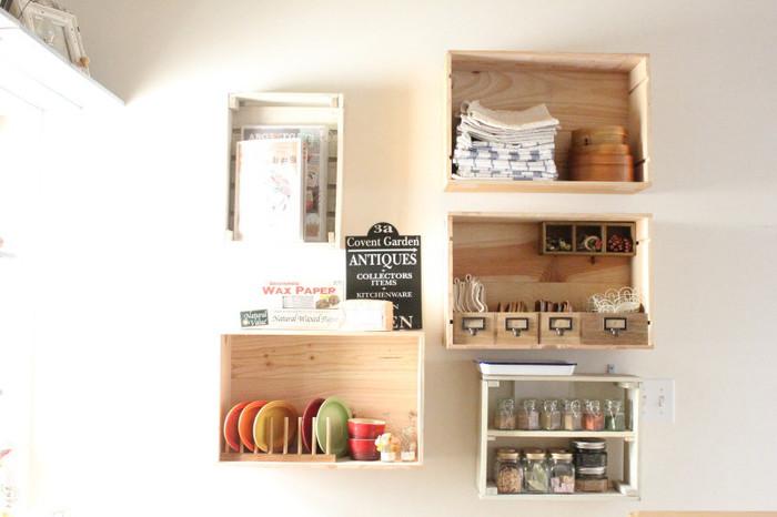 ここからは、おうちの各エリアでのワイン木箱のDIY例を見ていきましょう。こちらは、ワイン木箱を使った壁掛けの棚に、キッチン用品を仕分けして収納しています。美しくて使い勝手のいいアイデアですね。