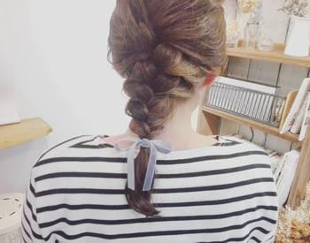 トレンドのベロア素材を、リボンのヘアアクセサリーで取り入れて。硬めに編んだ編み下ろしを、ソフトで女性らしい印象に導きます。