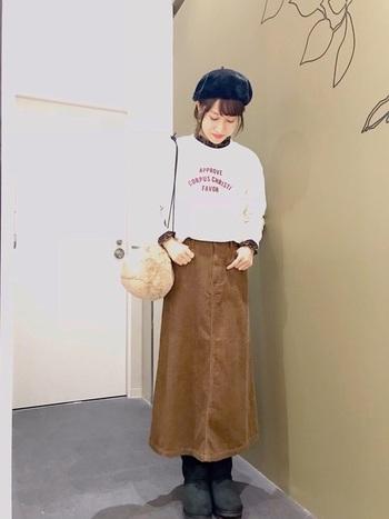 ロゴ入りスウェットとコーデュロイスカートなんていう休日ルックは、ブラック小物の力で落ち着き感を演出。衿元と袖から覗かせたチェックのシャツが、良いアクセントになっています。