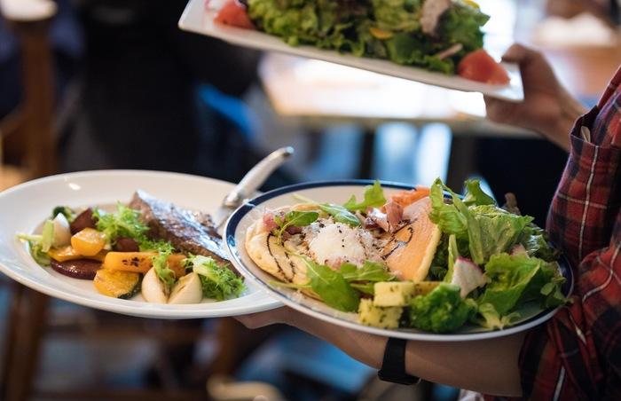 その日のサラダランチにパンケーキ、そしてステーキのプレートが厨房からテーブルへ駆け巡っています。ここまでボリューミーな野菜をいただけるのも麹町カフェならでは。