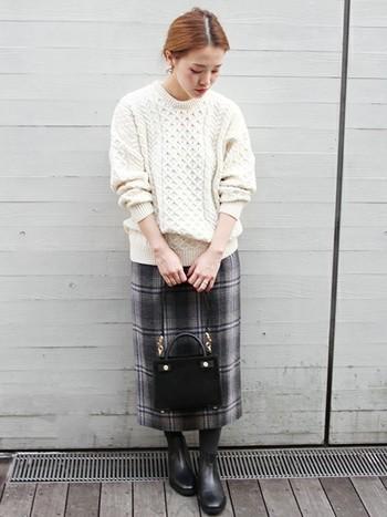 こちらは立体的な模様が美しいアラン編みニットに、旬度抜群のチェック柄スカートを合わせたきれいめカジュアル。アイルランドの伝統的なアランセーターは、程よいボリューム感とざっくりした素朴な風合いも大きな魅力。デニムにもスカートにも合わせやすいので、一枚で色々な着こなしが楽しめそうですね。