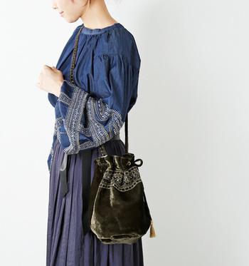 ベロア素材のバッグも、トレンド感や季節感のアピールに使える優秀アイテム。小ぶりな巾着バッグでベロアをプラスすれば、控えめな存在感で、しっかりおしゃれな印象に。